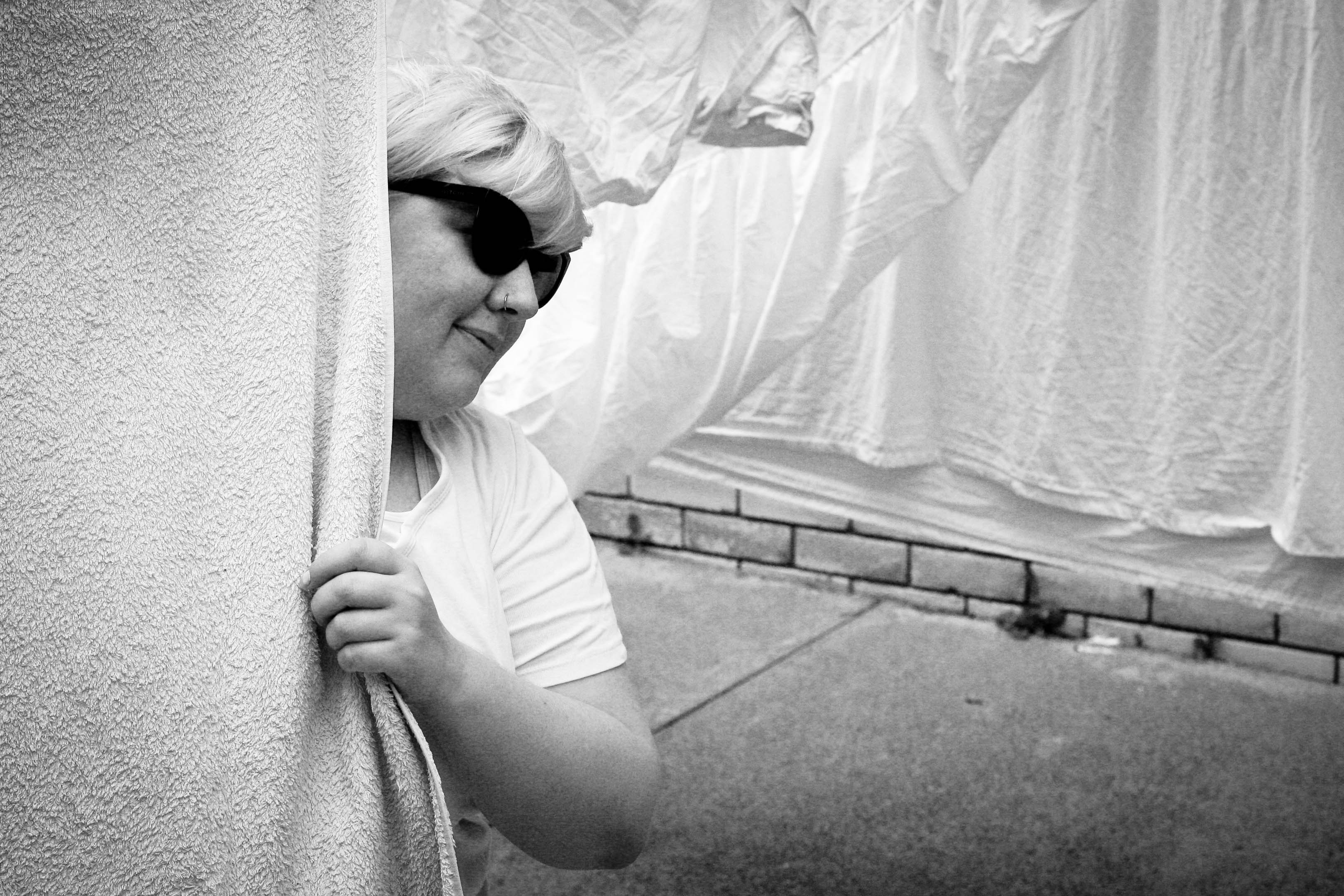 A black and white photo of me wearing sunglasses and peering around a towel on the line.
