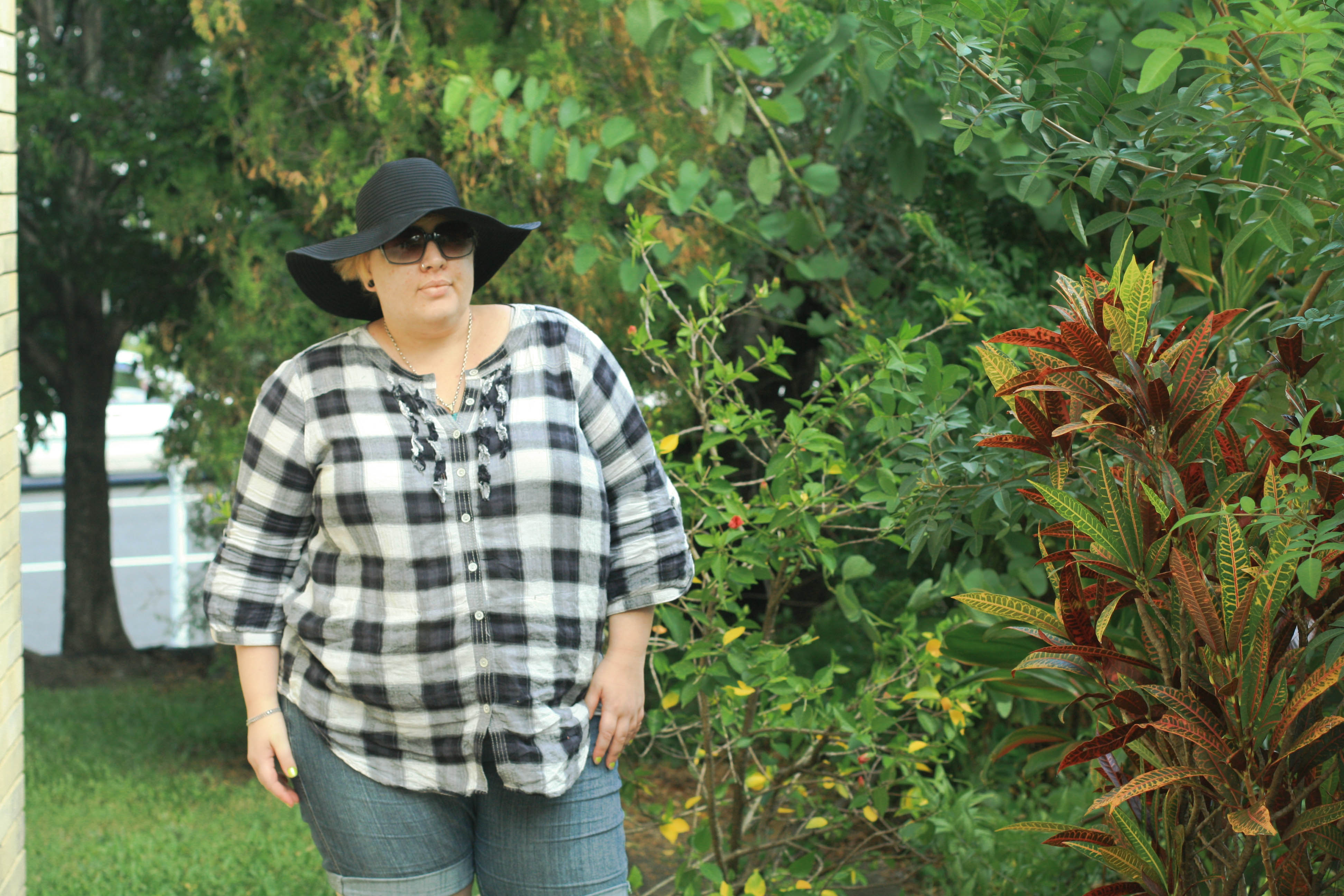 Photo of me standing in the garden wearing a black and white tartan tunic with shorts and a big black hat.