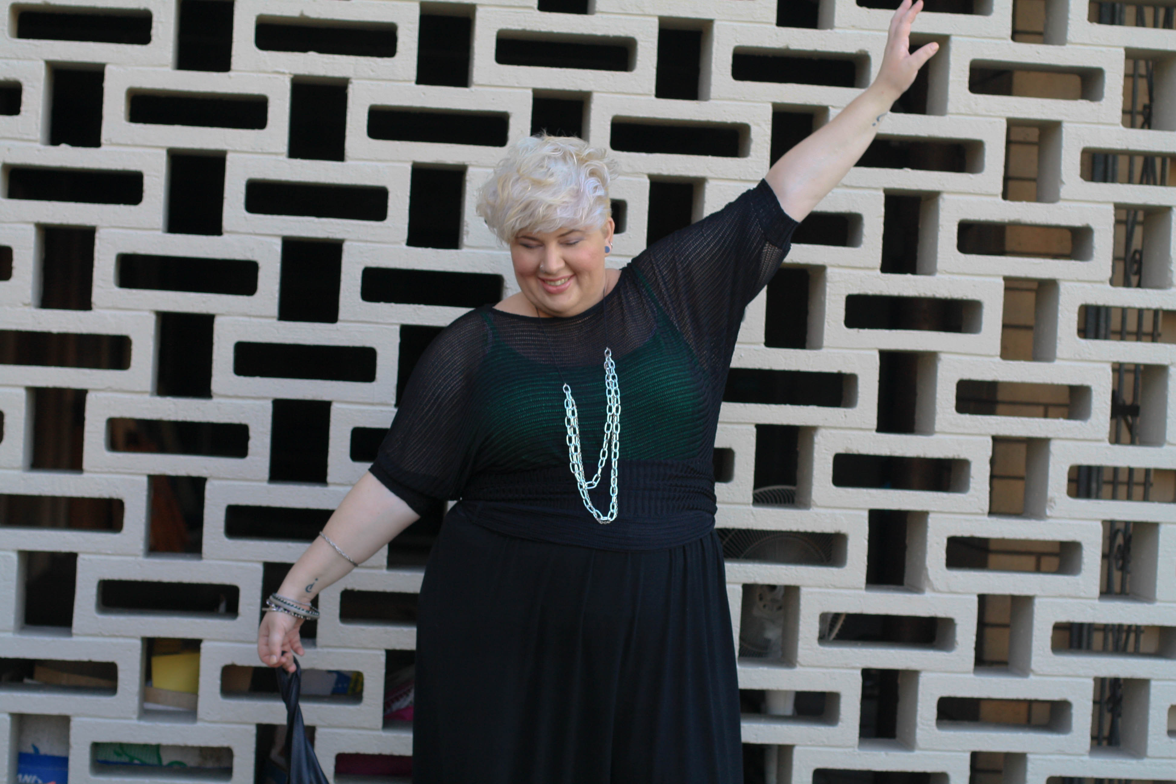 A photo of me, fat and pale skinned with short blonde hair, wearing a sheer black top with green singled under neath and large chain necklace. My arms are outstretched so you can see the baggy sleeve of the loose knit sheer top.