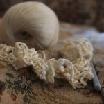 A photo of some cream yarn and crocheting on a floral tapestry couch.