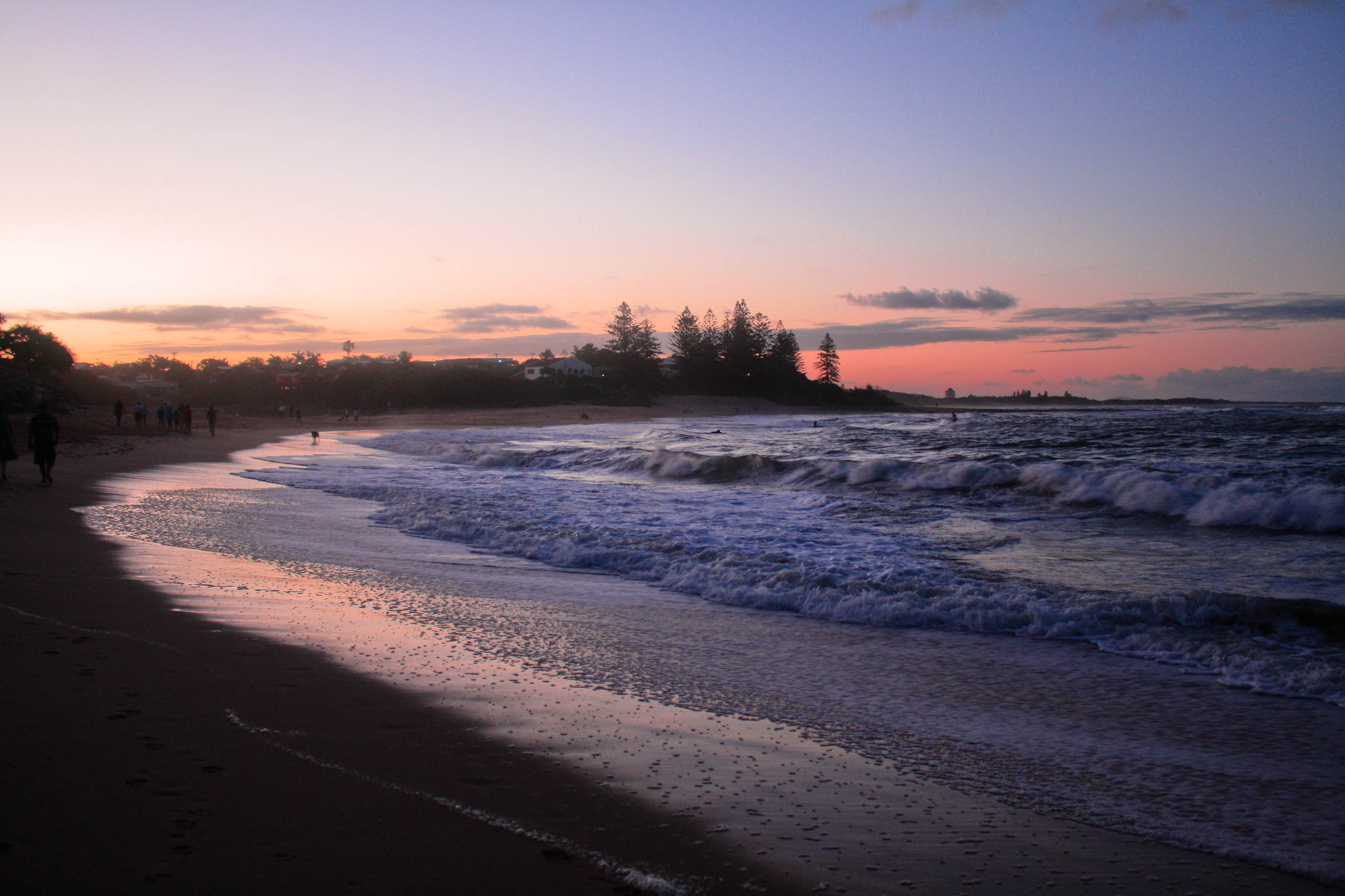 A photo of the waves rolling in at sunset. The beach curves around from the left foreground to middle background and the sky is a gradient of purple to pink.