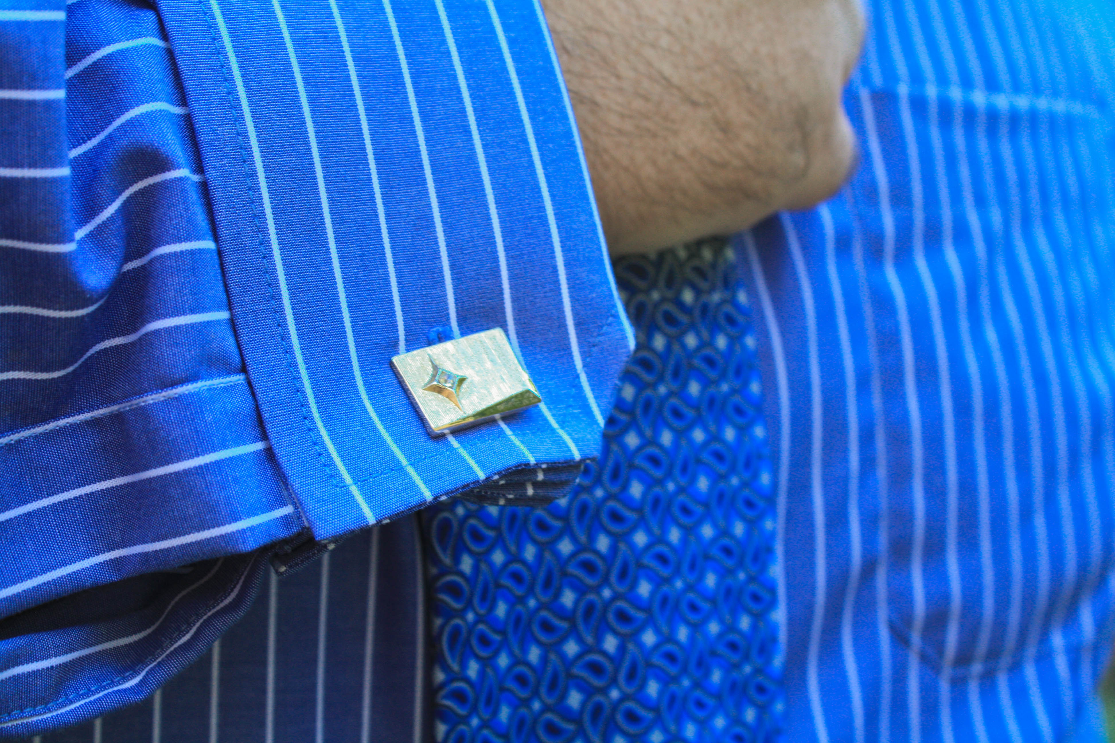 A close up photo of Nick's pinstriped shirt cuffs, secured with cuff links with a gem in them, and his blue paisley tie.