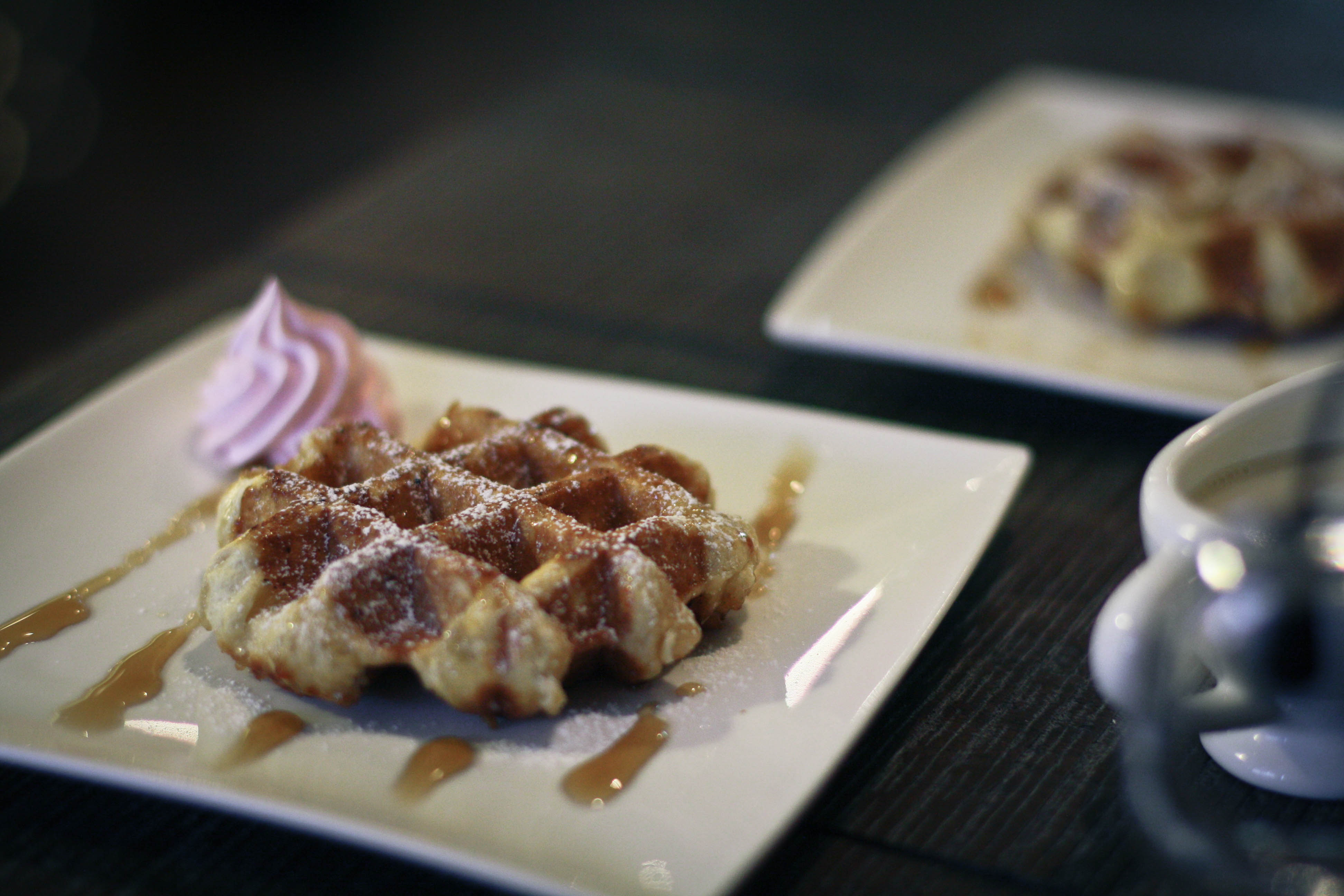 A photo of a square white plate with a delicious maple waffle drizzled in maple syrup and a little pink cream piped in the corner.