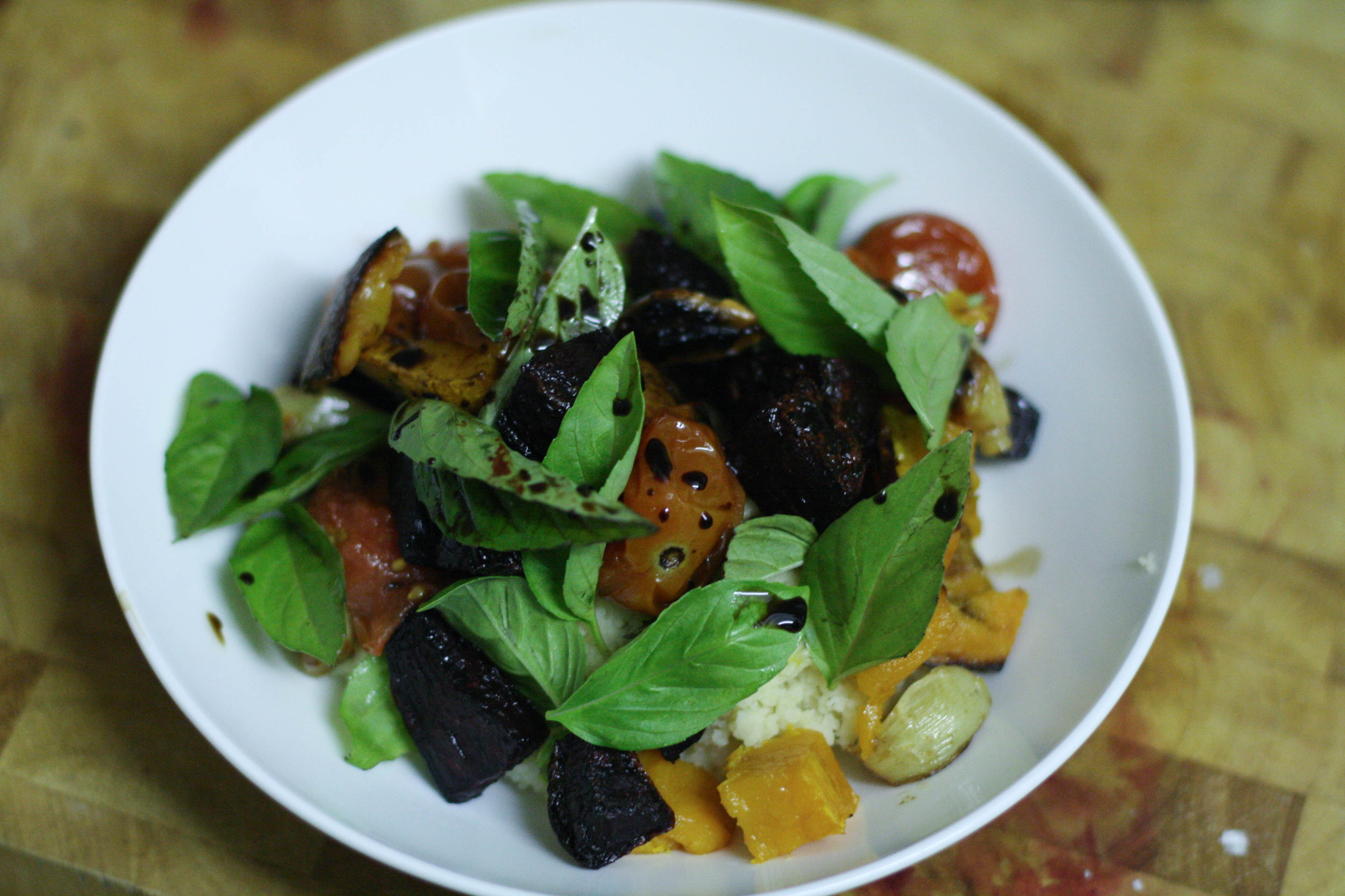 A photo of dinner: roast beetroot, pumpkin, garlic and cherry tomatoes on couscous served with balsamic vinegar reduction and many basil leaves.