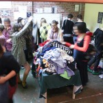 A photo of a room full of people moving about and holding up clothes that are piled on tables.