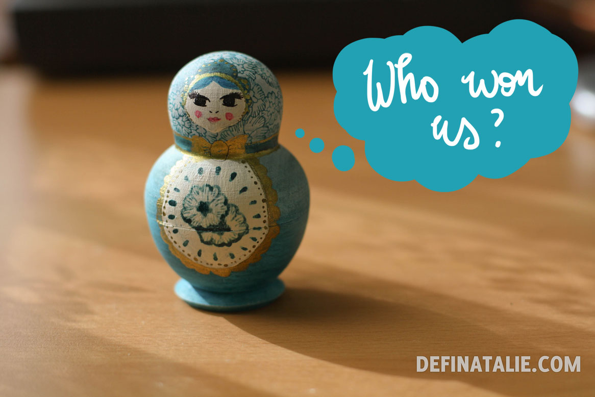 "A photo of the nesting doll with all dolls packed away inside. It's painted turquoise and white with gold accents and paisley motifs. Hand lettering in a thought bubble says, ""Who won us?"""