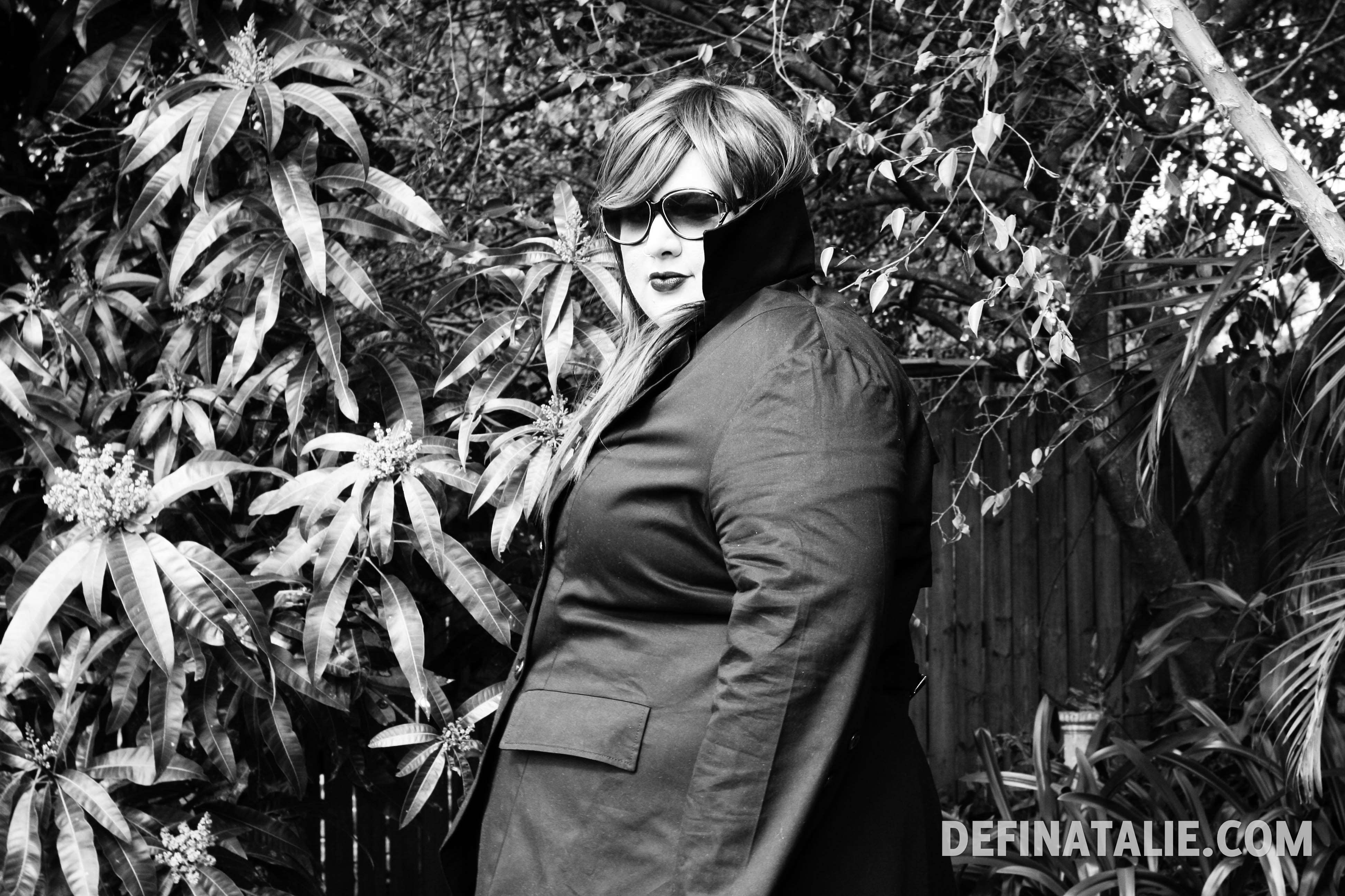 A photo of Natalie from the side peeking from behind the turned up collar of the jacket.