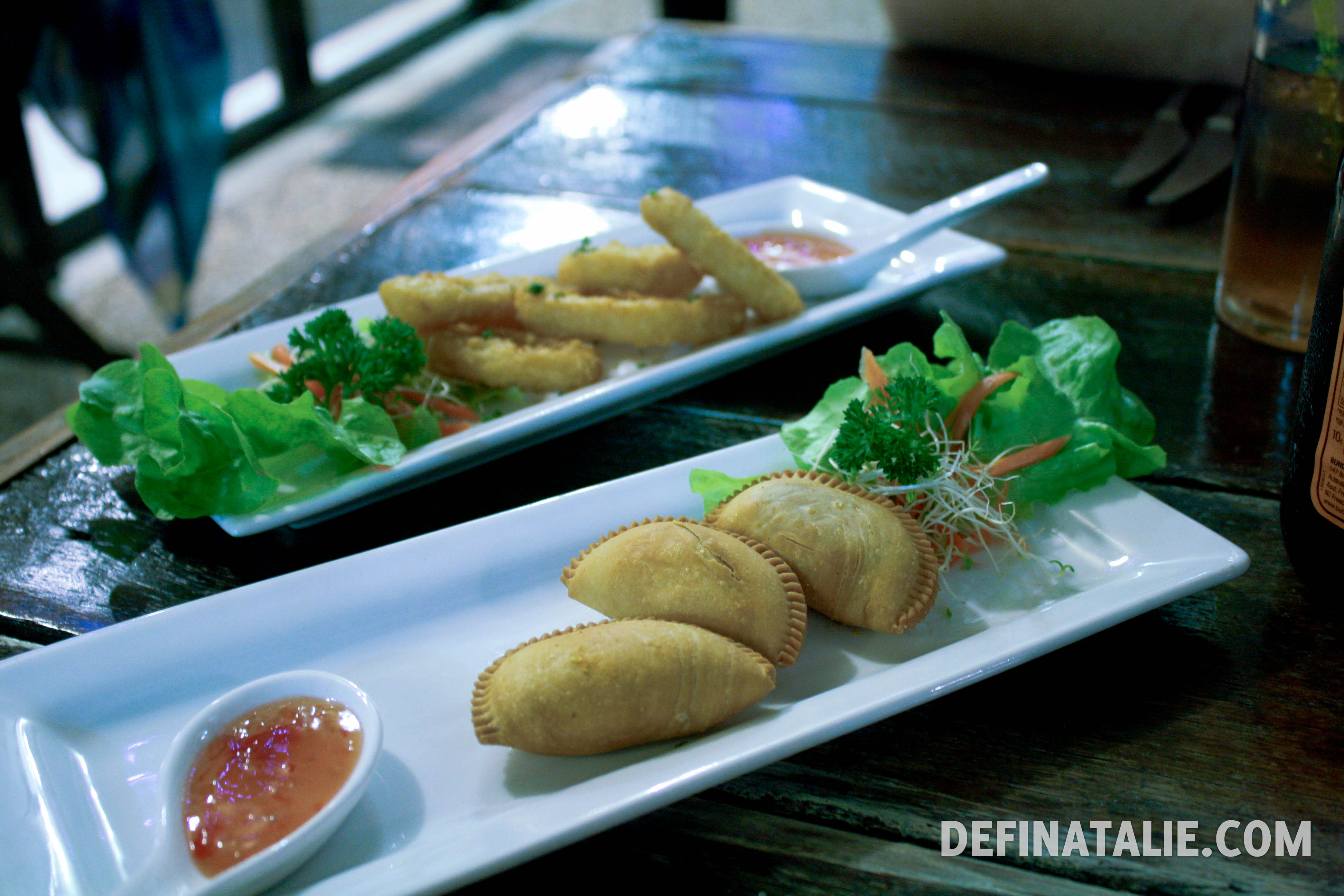 A photo of two entree dishes, calamari and vegetarian curry puffs.