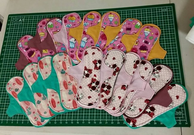 The eighteen exposed core cloth pads I made this weekend. They feature flannelette tops with lollies and sweets, dogs with sunglasses, and sweet little fern prints.