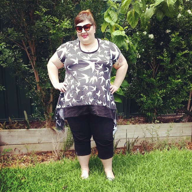 In my backyard (the trees are huge now!) wearing my black and white swallow t-shirt with some black cropped pants.
