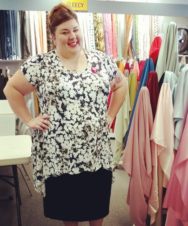 My boss took this photo of me at work, hence the lovely bolts of fabric! I'm wearing the jasmine print t-shirt here, and forcing myself to smile through the streams of constant snot!!