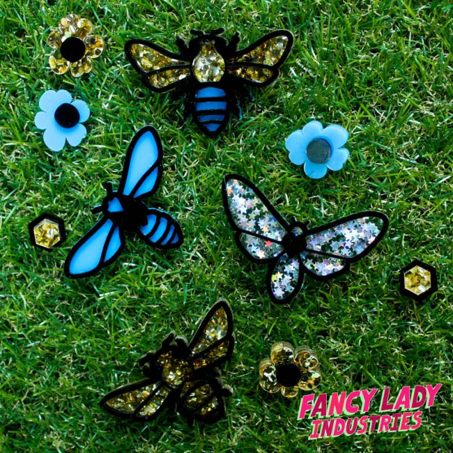 Laser cut moth, bee and wasp brooches amongst flower and honeycomb cell earrings, available on Fancy Lady Industries