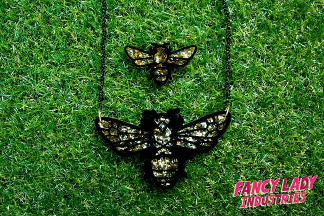 A Teddy Bear Bee necklace and brooch set made out of laser cut black and gold glitter acrylic, available on Fancy Lady Industries